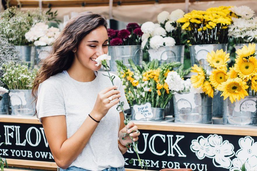 Szczęśliwa kobieta trzymająca kwiatek. Spełnia marzenia dzięki pożyczce.